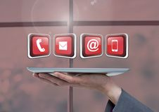 Businesswoman holding tablet with apps icons by window Stock Photos