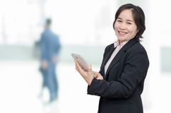 Businesswoman holding tablet computer and smiles Royalty Free Stock Photo