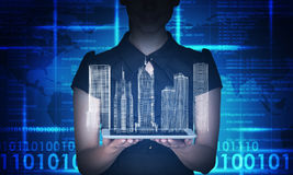 Businesswoman holding tablet and 3d city model. On abstract blue background Royalty Free Stock Images