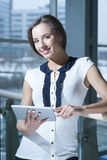 Businesswoman holding tablet device and smiling Stock Photography
