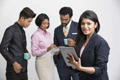 Businesswoman holding tablet with her colleagues. Cheerful businesswoman holding tablet with her colleagues on white background Stock Photos