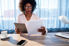 Businesswoman holding a tablet and reading a document Royalty Free Stock Images