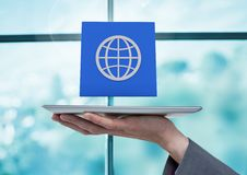 Businesswoman holding tablet with World global app icon by window. Digital composite of Businesswoman holding tablet with World global app icon by window Royalty Free Stock Image