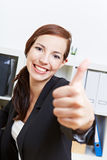Businesswoman holding thumbs up. Happy businesswoman holding her thumbs up in the office Royalty Free Stock Photos