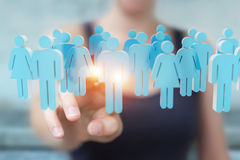 Businesswoman holding and touching 3D rendering group of blue pe. Businesswoman on blurred background holding and touching 3D rendering group of blue people Stock Image