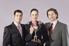 Businesswoman Holding Trophy With Male Colleagues Royalty Free Stock Photos