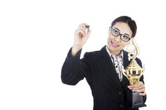 Businesswoman holding trophy writing on copyspace Royalty Free Stock Image