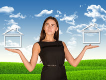 Businesswoman holding two houses as if chosing Stock Photography