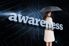 Businesswoman holding umbrella behind the word awareness Royalty Free Stock Image