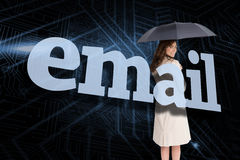 Businesswoman holding umbrella behind the word email Stock Photography