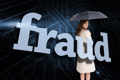 Businesswoman holding umbrella behind the word fraud Royalty Free Stock Photo