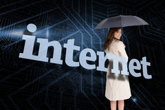 Businesswoman holding umbrella behind the word internet Stock Photography