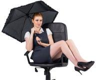 Businesswoman holding umbrella sitting on swivel chair Stock Image