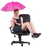 Businesswoman holding umbrella sitting on swivel chair. On white background Royalty Free Stock Photos