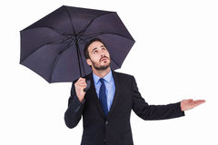 Businesswoman holding umbrella while testing if it rains Royalty Free Stock Image