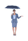 Businesswoman holding umbrella while testing if it rains Royalty Free Stock Images