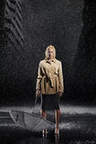 Businesswoman Holding Umbrella Upside Down In Rain. Full length portrait of a young businesswoman holding umbrella upside down in rain Stock Images