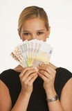 Businesswoman holding up Euros Stock Photography