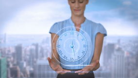 Businesswoman holding virtual alarm clock. With city on background stock video