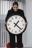 Businesswoman holding wall clock. Royalty Free Stock Photos