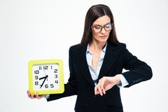 Businesswoman holding wall clock and looking on wristwatch Stock Photography