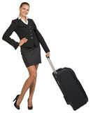 Businesswoman holding wheeled bag, hand on hip Royalty Free Stock Image
