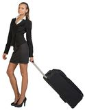 Businesswoman holding wheeled bag in moving Stock Photos
