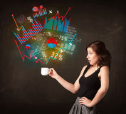 Businesswoman holding a white cup with diagrams and graphs Royalty Free Stock Photography