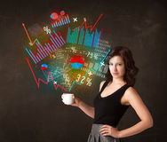 Businesswoman holding a white cup with diagrams and graphs Stock Image