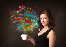 Businesswoman holding a white cup with diagrams and graphs Royalty Free Stock Photos