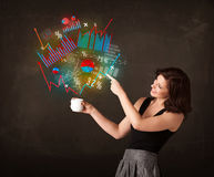 Businesswoman holding a white cup with diagrams and graphs Stock Photography