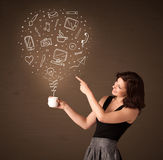 Businesswoman holding a white cup with social media icons Stock Photography