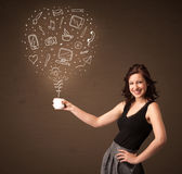 Businesswoman holding a white cup with social media icons Stock Photo