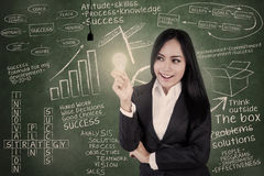 Businesswoman Holds Lit Bulb In Class Stock Photo