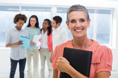 Businesswoman holds planner and smiles at camera while colleagues stand behind Royalty Free Stock Image