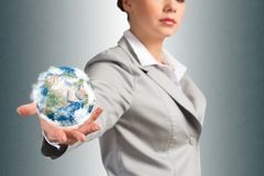 Businesswoman holds up a planet Earth Stock Photo