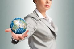 Businesswoman holds up a planet Earth Stock Photography