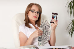 Businesswoman with hourglass and money Royalty Free Stock Image