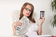 Businesswoman with hourglass and money Stock Image