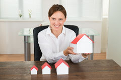 Businesswoman With House Models On Desk Royalty Free Stock Image