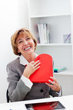 Businesswoman hugging a red heart present. Stock Photo