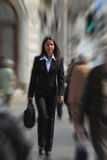 Businesswoman in a hurry. Businesswoman walking quickly in a crowded downtown.The image presents a significant spin blur effect to accentuate the dynamism of the Royalty Free Stock Photos