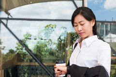 Businesswoman in a hurry holding coffee and looking at her watch Royalty Free Stock Images