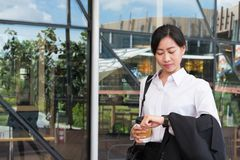 Businesswoman in a hurry holding coffee and looking at her watch Stock Photo