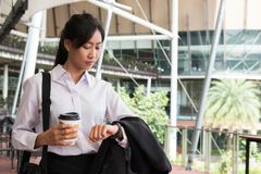 Businesswoman in a hurry holding coffee and looking at her watch Royalty Free Stock Image