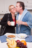 Businesswoman with Husband In Kitchen Stock Images