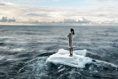 Surfing sea on ice floe. Mixed media. Businesswoman on ice block floating in sea . Mixed media Royalty Free Stock Photos