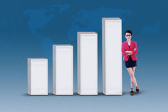 Businesswoman and increasing bar chart on blue Stock Photo