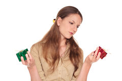 Businesswoman - indecision gifts. Isolated studio shot of a Caucasian businesswoman making a difficult choice between a red present and a green present royalty free stock images