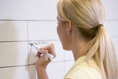 Businesswoman indoors writing on erasable board Royalty Free Stock Photos